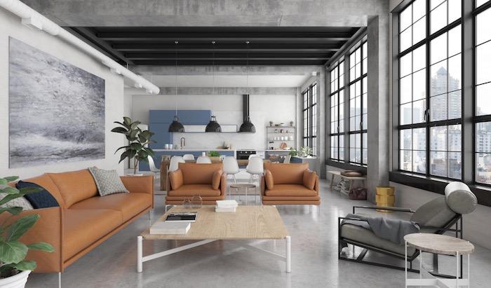 cuisine ouverte sur salon salle à manger avec des meubles industriels, canapé et fauteuils en cuir marron, table basse bois, chaise longue grise, murs effet beton