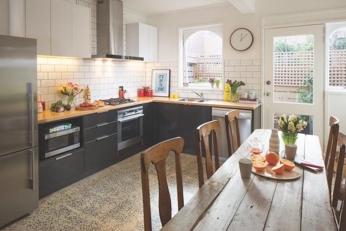 comment amenager une cuisine blanche et noire avec meuble bas noir, credence carrelage blanc, aspirateur inox, plan de travail bois, table et chaises bois rustique