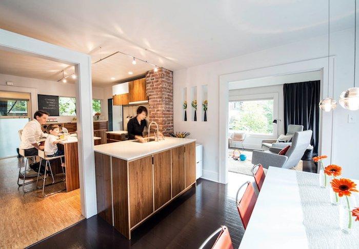 cuisine bois avec ilot central, colonne en briques, luminaire éclairage spots, ouverture sur une salle à manger moderne