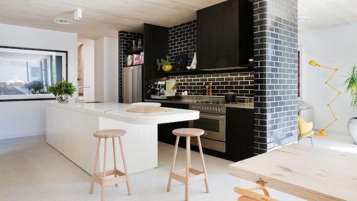 cuisine moderne blanche et noire, meuble cuisine et mur en briques noir, ilot central blanc avec des tabourets en bois, sol gris