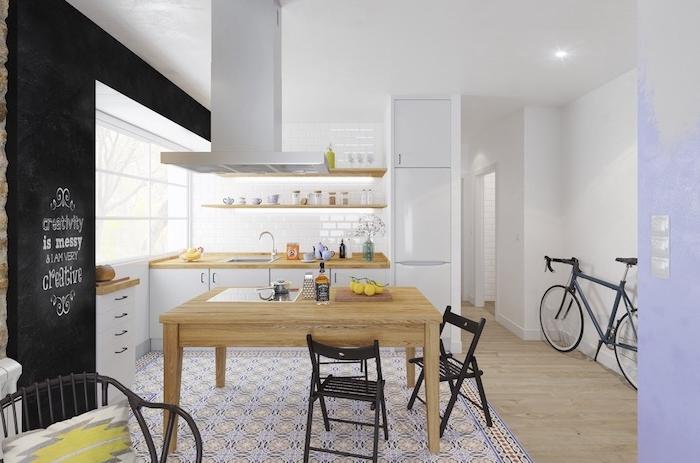 cuisine moderne blanche en bois et blanc, mur repeint de peinture ardoise tableau noir, tapis motifs geometriques, table en bois clair, plan de travail bois, etageres ouvertes, style scandinave