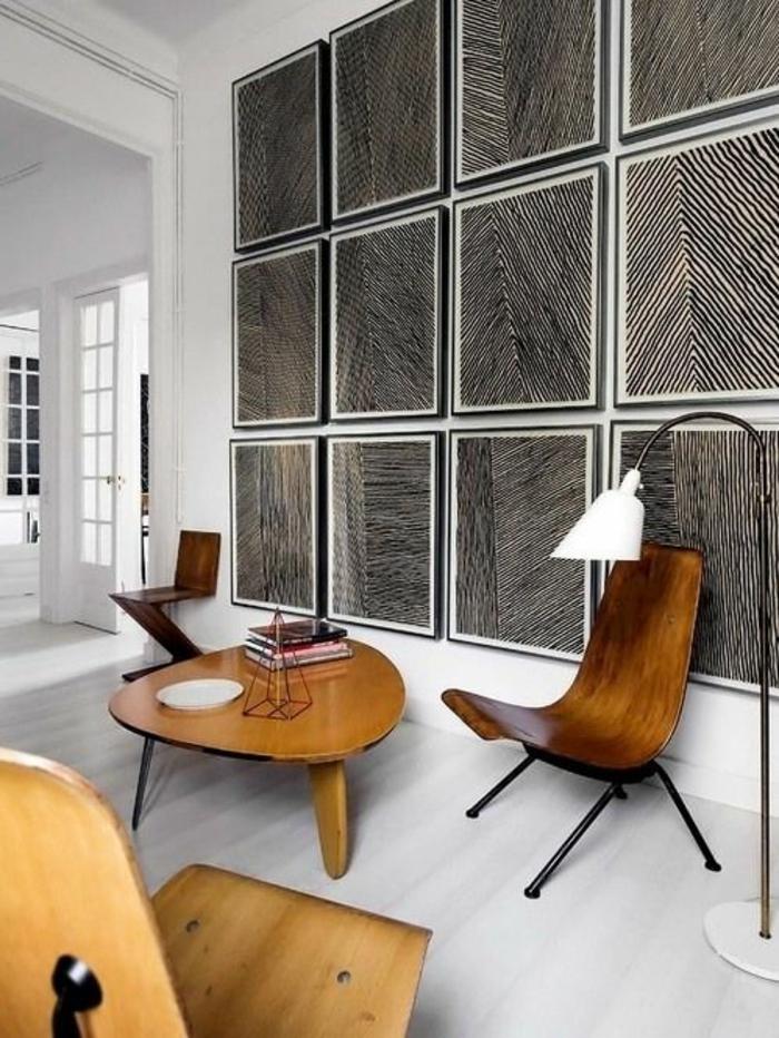 salon moderne de luxe avec des fauteuils en bois au design sophistiqué, murs avec des panneaux carrés en noir et blanc, parquet blanc, table en bois claire avec forme ronde irrégulière, luminaire sur pied avec abat-jour blanc