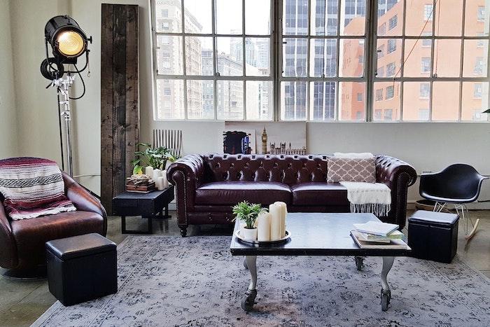déco loft industriel dans un salon avec canapé en cuir vintage marron foncé, fauteuil en cuir, chaise a bascule scandinave, table basse minimaliste, projecteur, granges fenetres, planches bois deco