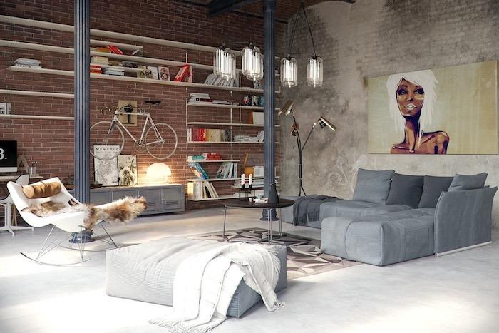 ambiance artistique dans un salon industriel, suspension bocal, canapé gris, chaise à bascule avec jeté de fourrure, mur en briques, etagere industrielle, tableau mur portrait femme abstrair