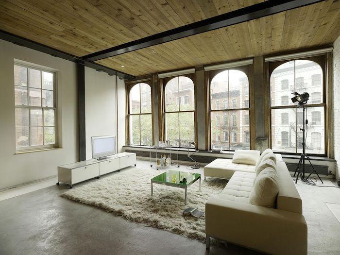 exemple de déco loft industriel dans un salon spacieux avec canapé beige, tapis moelleux blanc, table basse en metal et verre, meuble tv blanc, grande baies vitrées, plafond en bois