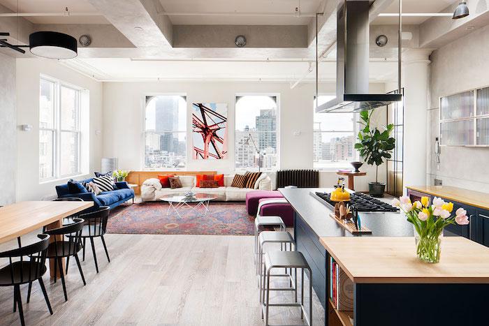 exemple de salon déco loft industriel avec canapé blanc cassé, deçoré de coussins rouge marron et noir, tapis oriental, canapé bleu marine, table basse en verre, cuisine ouverte