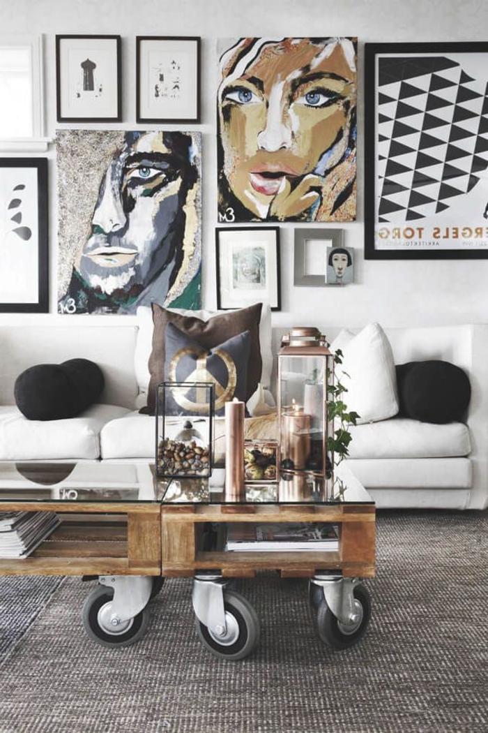 salon moderne mixant le style graphique et le style scandinave accentuant sur le mur en cadres et la table basse palette
