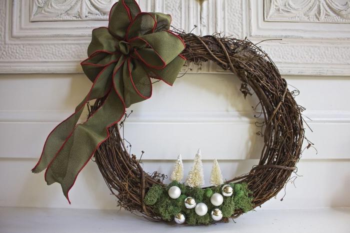 une couronne de l'avent réalisée en branchage et décorée de mousse artificielle et de sapin décoratifs, projet diy noel inspirée de la nature
