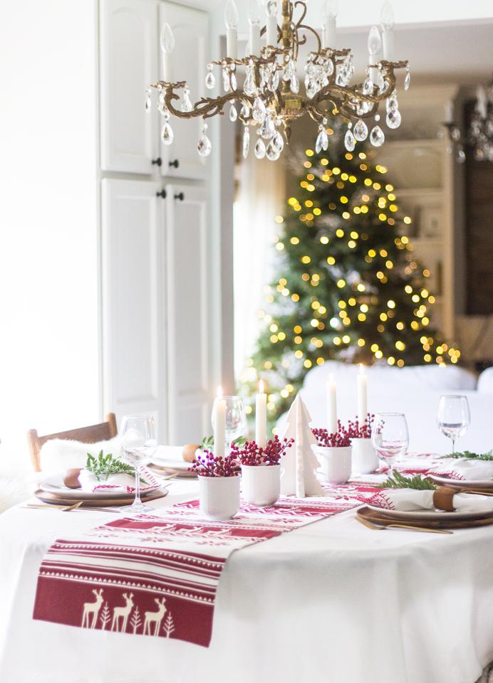une table de noël rouge et blanc d'un style scandinave traditionnel avec son chemin de table aux motifs nordiques de saison