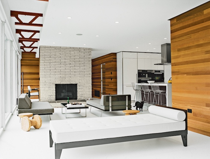 deco style industriel dans un salon avec canapé gris, chaise longue gris et blanc, table basse noire, cheminée en pierre, murs en bois clair