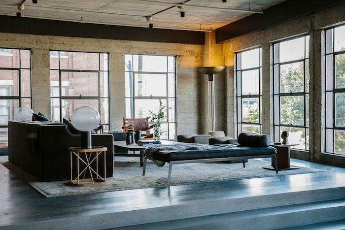 deco stule industriel dans un salon spacieux avec canapé couleur foncée, table basse bois, chaise longue en metal et matelas bleu, murs effet beton