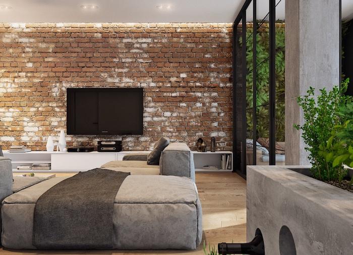 deco style industriel salon avec murs en briques, parquet bois clair, canapé gris, meuble tv blanc, verriere noire
