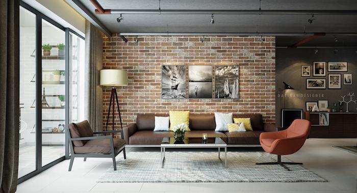 exemple de salon style industriel avec mur en briques, canapé en cuir, tapis gris, fauteuil rouge, deco murale de tableaux noir et blanc, spots