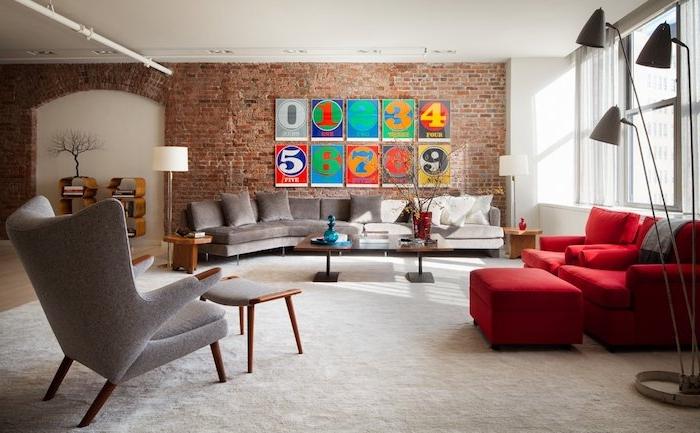 décoration industrielle salon avec canapé gris et canapé rouge, tapis blanc, tables basses en bois, deco murale de cadres avec chiffres colorés