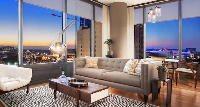 salon style industriel avec canapé gris avec coussins décoratifs, table basse en bois, tapis noir et blanc, fauteuil blanc, suspension bocal, lampe industrielle