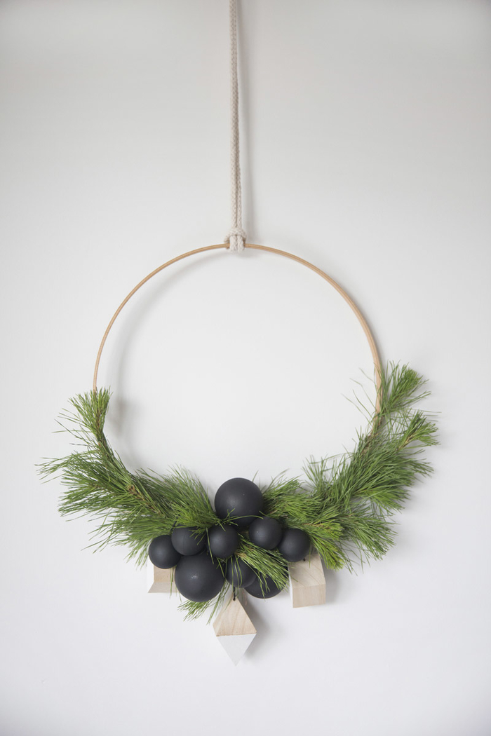couronne de noël faite maison d'inspiration scandinave et minimaliste décorée de branches de verdure et de perles en bois, idée deco noel faire soi meme