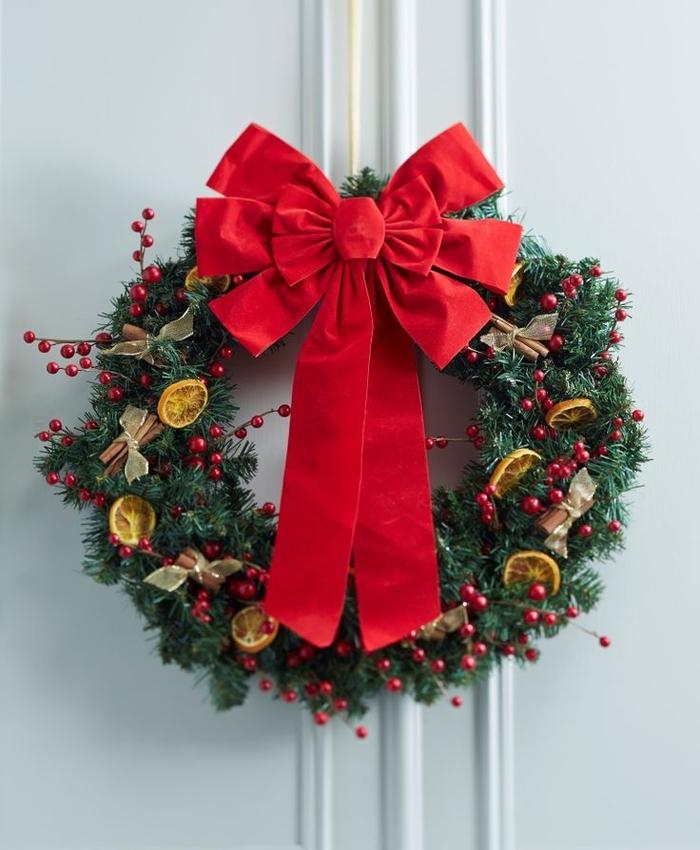 jolie couronne de l'avent traditionnelle en verdure, oranges séchées, bâtons de cannelle et fruits rouges artificiels agrémentée d'un ruban rouge, deco de noel a faire sois meme