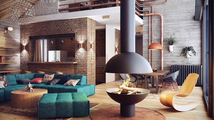 modele de salon industriel avec canapé et tabourets bleu canard, table basse en bois rond, cheminée design, mur en briques pour séparer la cuisine, chaise longue bois, parquet clair