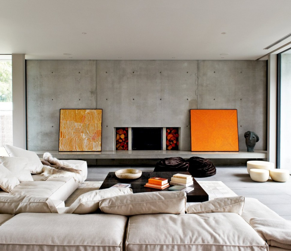 meuble industriel , petite table bassse en bois, canapés blanc cassé., cheminée sur un fond en beton, tableaux decoratifs orange et blanc
