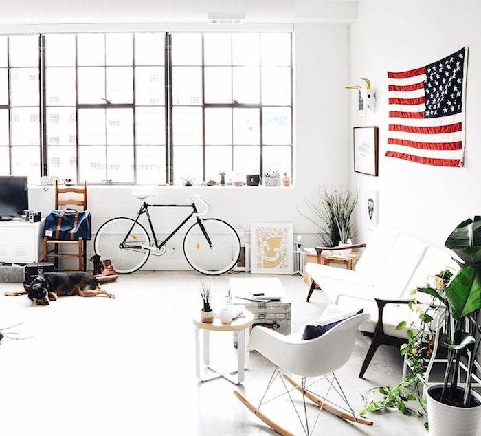 déco loft industriel avec des touches de deco scandinave, canapé blanc, chaise a bascule scandinave, table basse coffre vintage, vélo, grande fenetres, drapeau etats unis, sol blanc