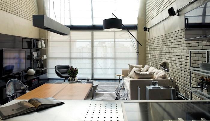 etagere industrielle dansun salon style industriel avec canapé blanc cassé., table basse ronde, chaise en cuir noire, suspension originale, mur en briques blanches