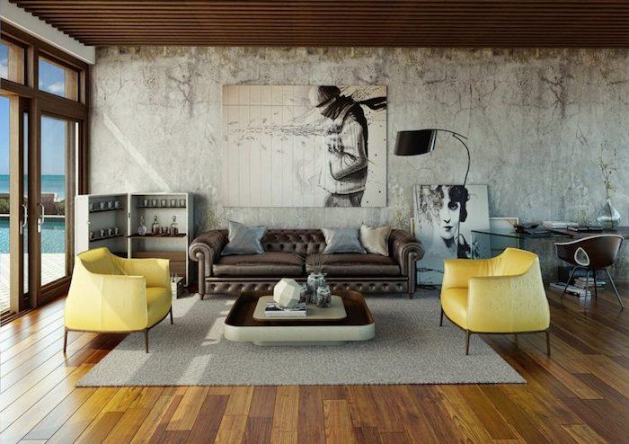 décoration industrielle salon avec canapé en cuir marron foncé, fauteuils jaunes, tapis gris, sol en parquet marron, mur usé, plafond en bois, cadres tableaux graphiques en noir et blanc