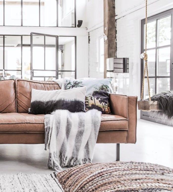 décoration industrielle salon avec canapé en simili cuir noir décoré de couverture gris et blanc et coussins decoratifs, coussins tricot, poutre apparente, balançoire intérieur