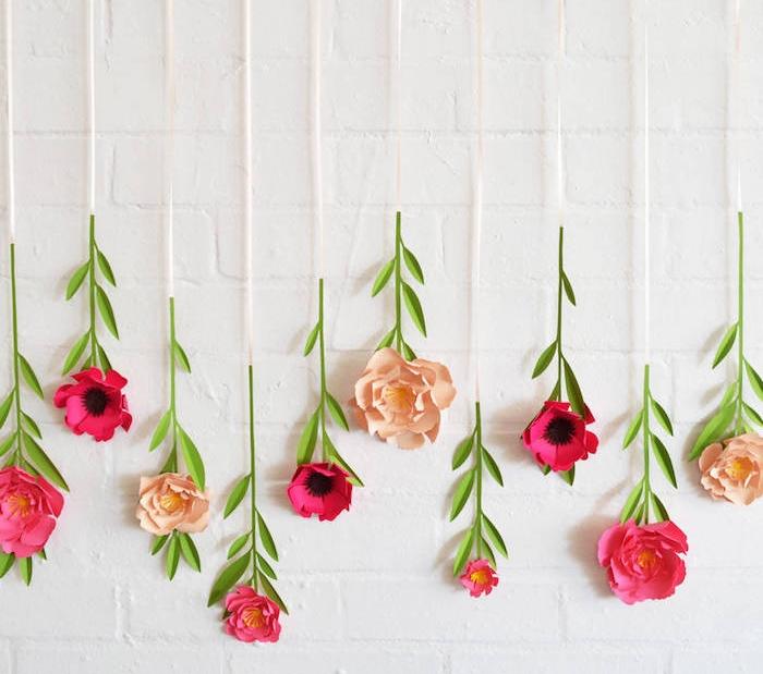 exemple de deco murale de fleurs suspendues, diy fleur en papier crème et fuchsia, mur en briques blanche
