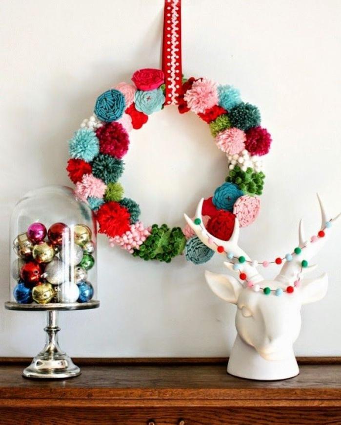 jolie couronne de noel a faire soi meme composée de pompons en laine colorés et de roses au crochet