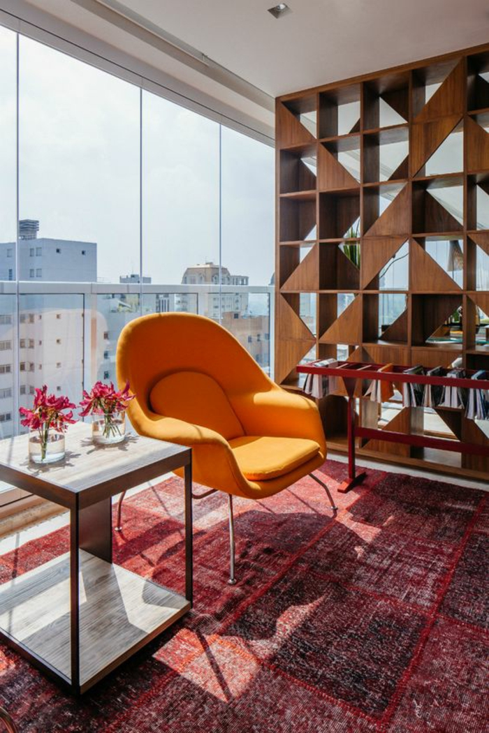 amenagement salon avec tapis en rouge et noir, fauteuil orange avec des pieds en métal, table carrée avec deux niveaux, séparateur d'espace aux motifs formes géométriques en bois marron, table rectangulaire en métal rouge