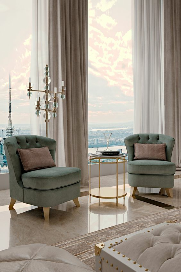 deco salon design avec deux grands fauteuils en vert pistache, sol recouvert de marbre beige lisse et brillant, table ronde avec base haute en métal doré, luminaire sur pied en métal doré avec des boules en verre, rideaux en gris perle