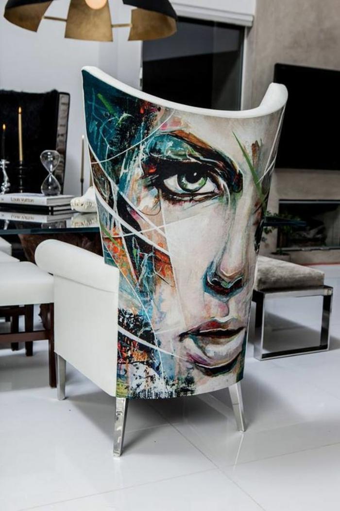amenagement salon avec grand fauteuil au dossier au visage de belle femme portrait en couleurs vives nuances du bleu et du vert, sol aux dalles carrelage blanc brillant, cheminée en couleur taupe, luminaire en couleur dorée