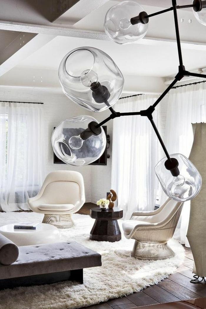salon moderne de luxe, deux fauteuils en cuir blanc, grand luminaire en métal noir avec des grandes boules en verre blanc, dormeuse avec coussin long et rond, plafond divisé en quelques carrés, parquet en marron foncé