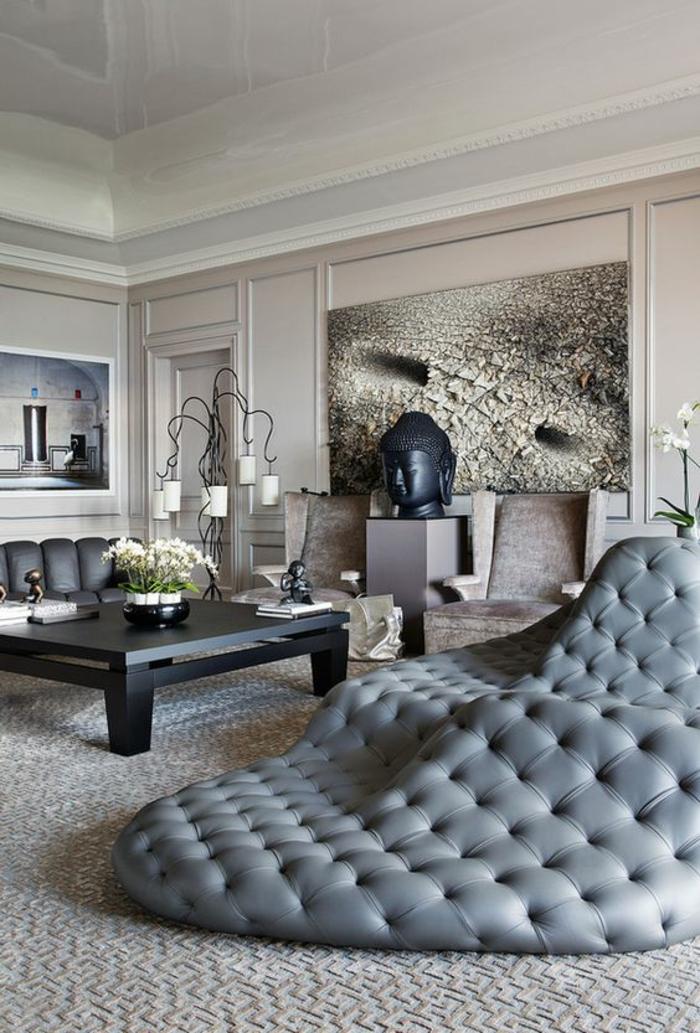 maison moderne de luxe, dormeuse énorme design en gris perle, avec effet matelassé, tableau au mur en blanc et gris. table carrée en noir, murs en beige