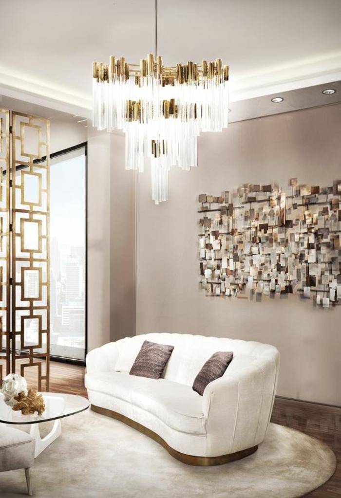 salon de luxe haute brillance avec panneau en métal en couleur argent, grand luminaire en métal doré et pampilles longues en cristal, tapis rond e blanc, canapé en blanc avec deux coussins couleur violette