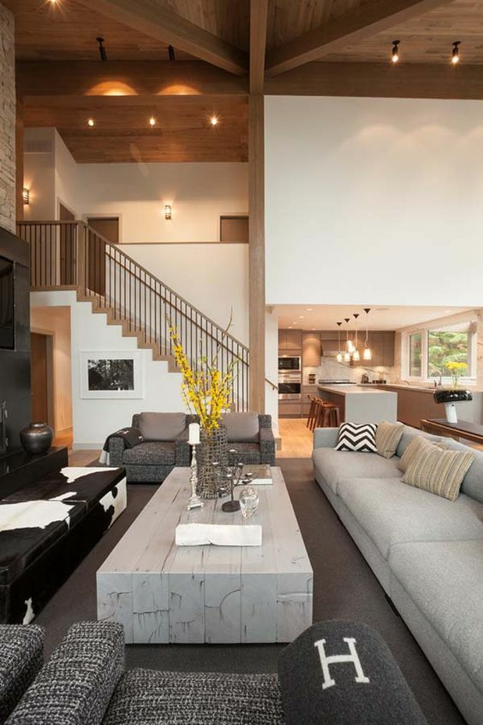 meuble salon pas cher, table rectangulaire en bois blanc, canapé blanc avec des coussins multicolores, canapé en imitation peau de vachette en noir et blanc, deux fauteuils en gris anthracite et en gris clair
