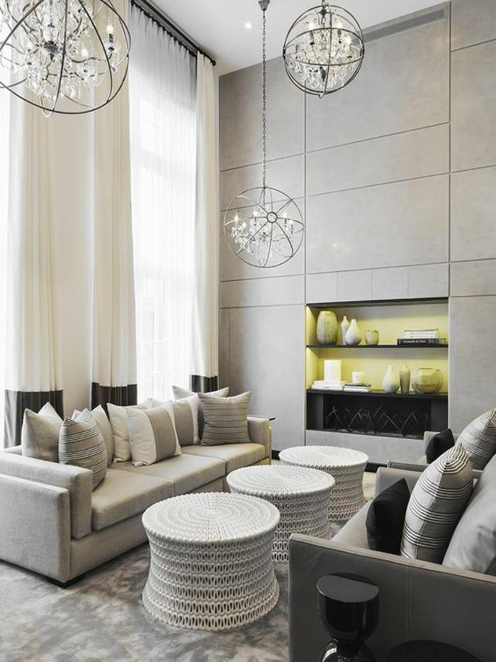 salon moderne de luxe avec des meubles en gris perle et trois tables en blanc avec des bases ajourées, des luminaires boules au plafond en métal noir, grand et haut mur avec bibliothèque, trois étagères ouvertes en verre noir