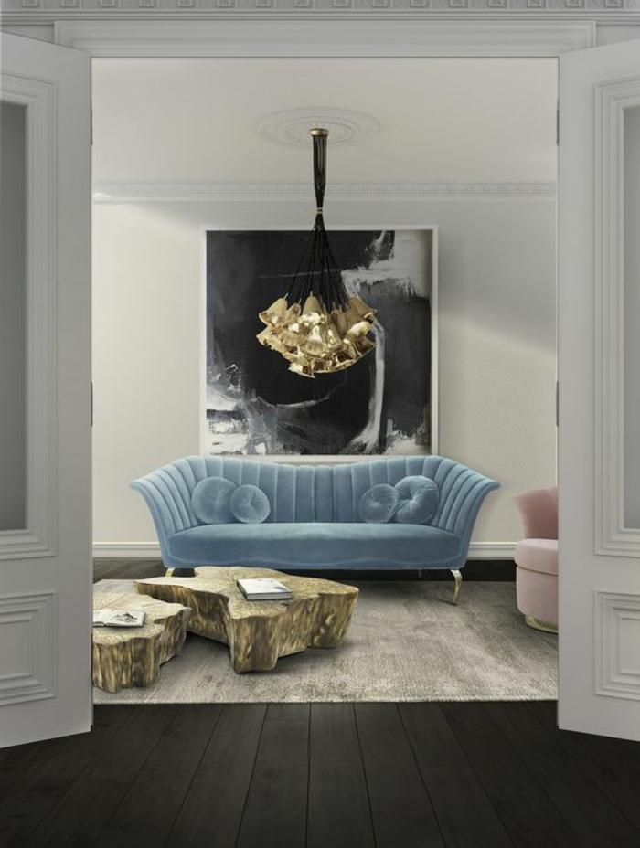 idée deco salon, salon moderne de luxe, canapé en bleu pastel en velours, fauteuil en forme semi-ronde en rose poudré, ambiance glamour avec luminaire plafond n forme d'une douzaine de clochettes dorées suspendues sur des fils qui forment un ruban noir, parquet noir