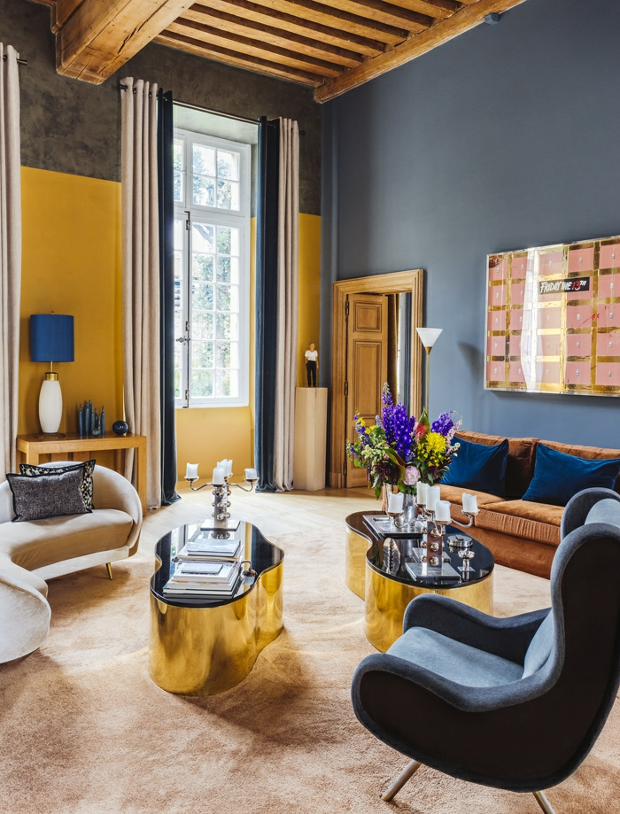 deco salon design avec des murs en bleu canard, une pergola en bis clair au plafond, des murs en jaune, deux tables comme deux moitiés d'un seul corps, en métal doré et plan en noir brillant, fauteuil en velours bleu, tapis en beige