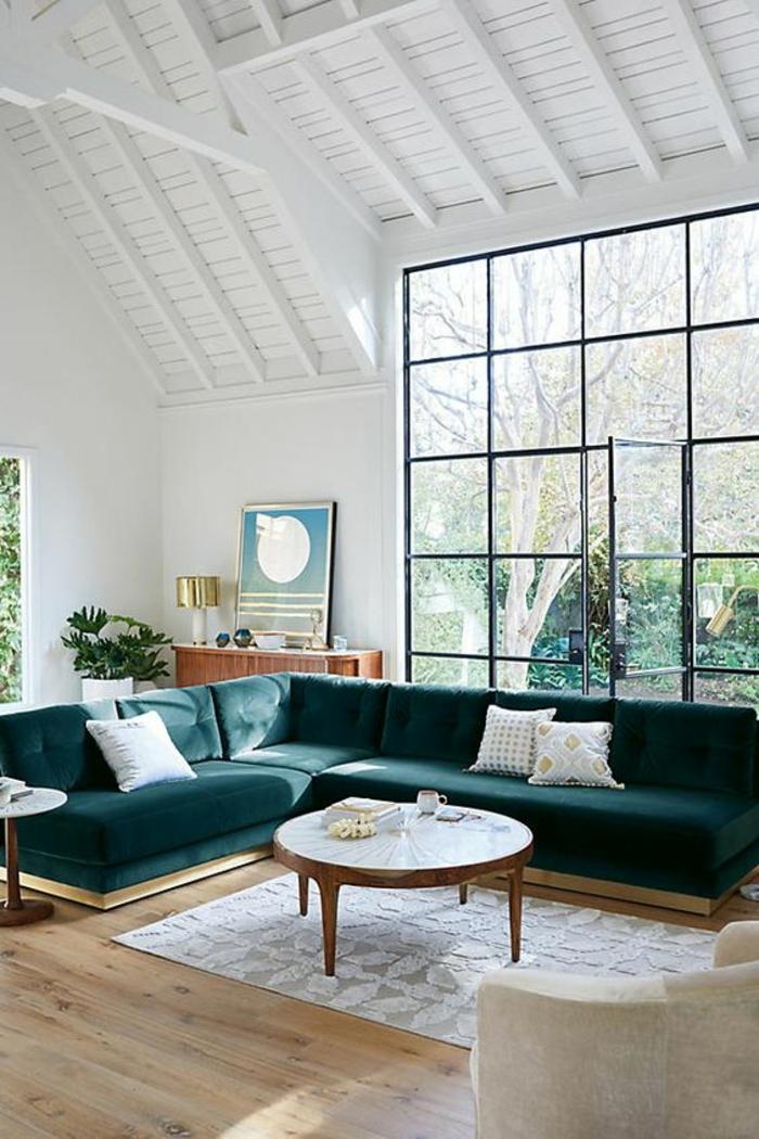 idée deco salon, meuble salon pas cher, tapis carré en gris et blanc, canapé angulaire en vert pétrole, table ronde avec plan en blanc, plafond en blanc, fauteuil en couleur blanc crème