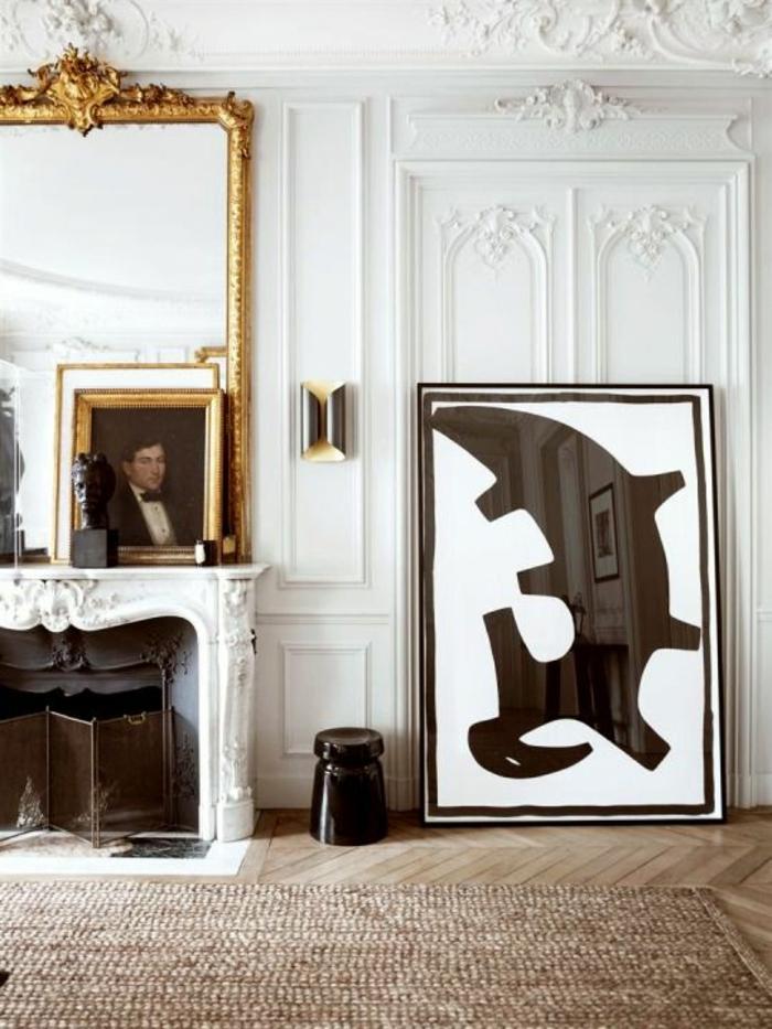salon moderne de luxe, avec tapis en couleur saumon, miroir au cadre doré avec des ornements floraux style Renaissance, cheminée blanche, murs et porte avec des frises blanches, tableau avec portrait d'homme du XV-ème, panneau décoratif miroir en noir et blanc avec figure abstraite