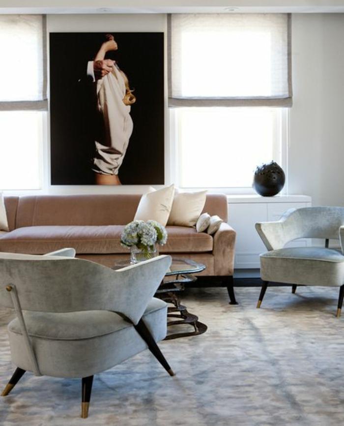 amenagement salon avec grande photo au mur qui représente un homme et une femme qui s'embrassent, tapis en beige et noir, fauteuils en couleur vert pistache, canapé en couleur saumon