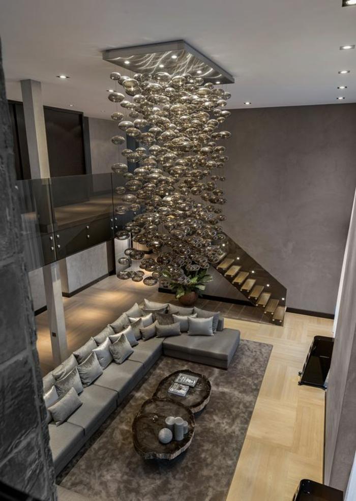 meuble salon pas cher, grand espace en deux niveaux, luminaire en suspension massif avec une multitude de boules en verre, tapis rectangulaire en couleur taupe, murs en couleur taupe, trois tables pour café en forme de troncs d'arbre