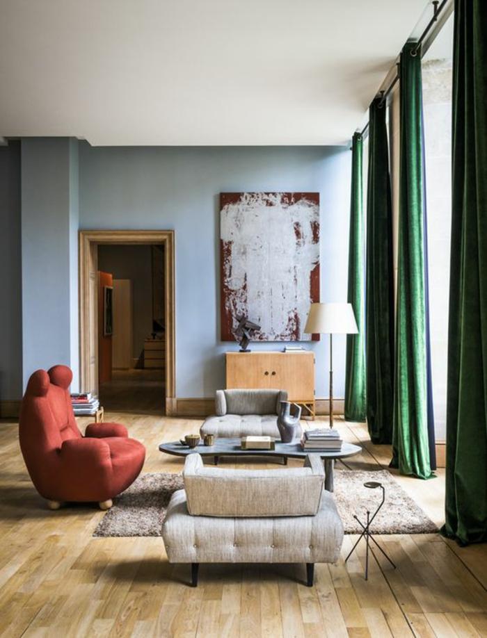 salon moderne de luxe, deco salon, fauteuil design en couleur brique, rideaux vert émeraude, tableau en rouge bordeaux et blanc, murs en bleu pastel, parquet en jaune