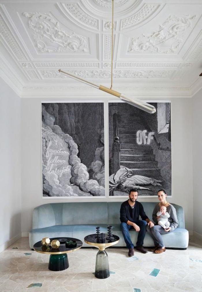 meuble salon pas cher, salon de famille qui est assise sur un canapé en velours en bleu pastel, plafond richement orné de frises blanches, luminaire en forme oblongue excentrique, carrelage en dalles art déco en couleur bleue et blanche, deux tables rondes avec plan noir et bases en verre