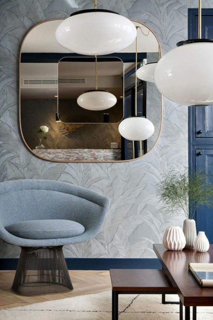 amenagement salon moderne de luxe, grand miroir en forme carrée au cadre doré, luminaire blancs boules, fauteuil en bleu pastel avec base rectangulaire transparente, tables en marron foncé
