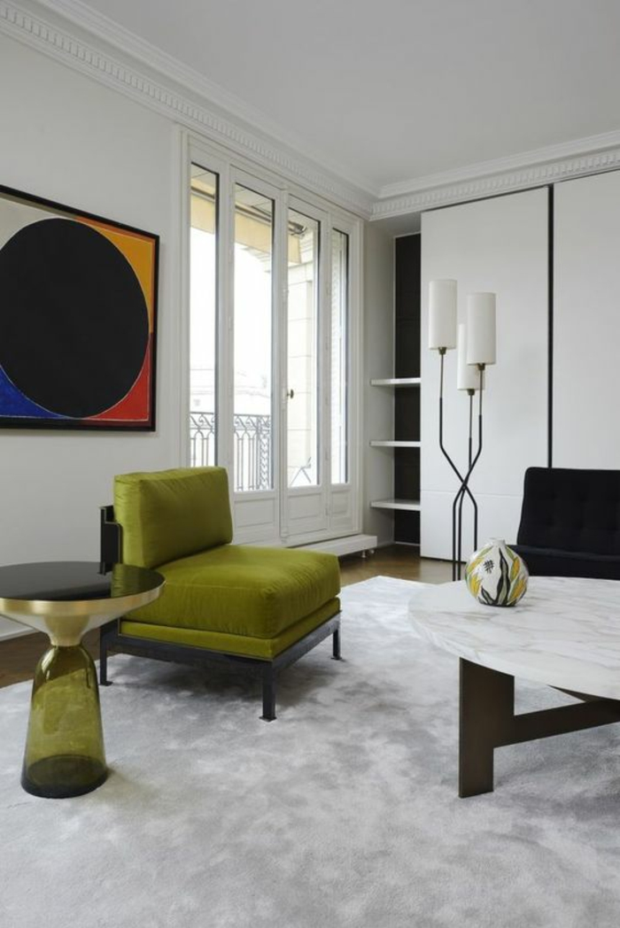 amenagement salon, deco salon design avec des meubles en vert olive, tableau avec des motifs abstraits en couleurs vives, table ronde avec plan en marbre, luminaire sur pied avec des abat-jours blancs et métal noir, tapis blanc