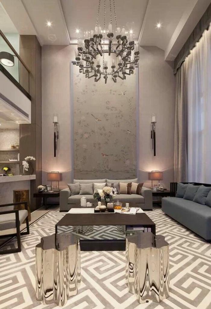 salon moderne de luxe, luminaire en forme de grand bougeoir rond, murs en rose pastel, sol en carrelage avec des motifs grecs, table avec des pieds en forme de troncs d'arbre en verre, canapé en couleur grise fumée, rideaux blancs transparents