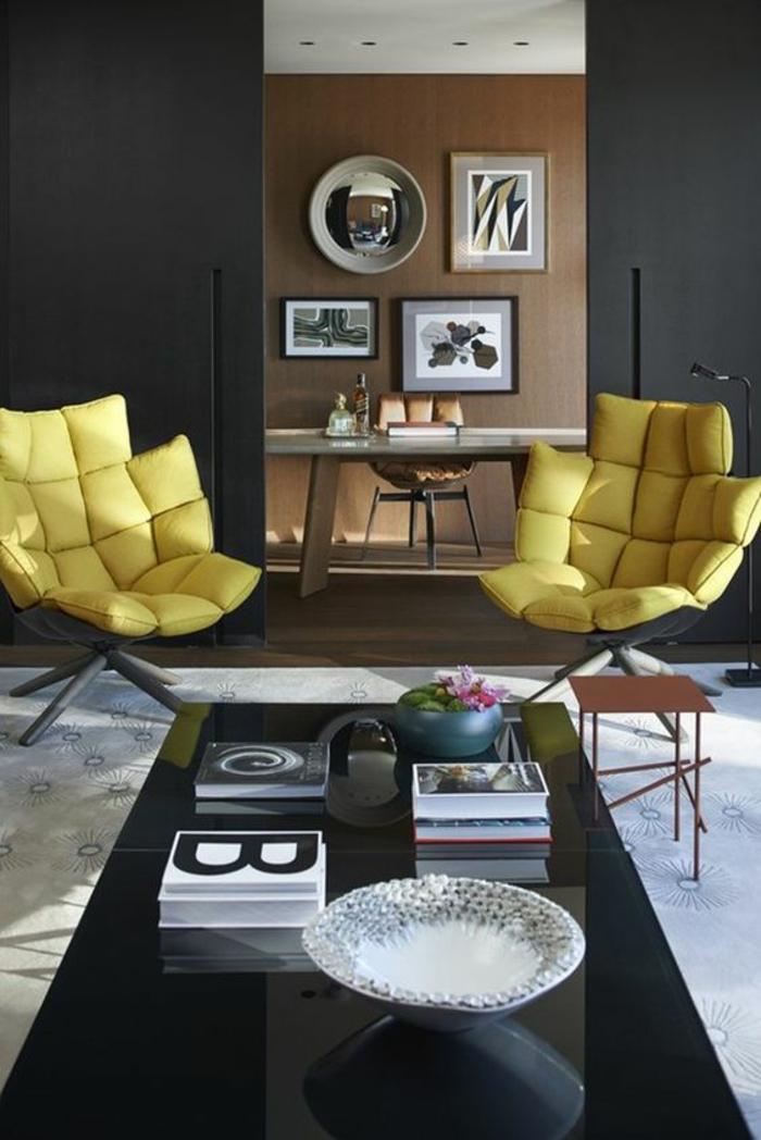 meuble salon pas cher avec deux grands fauteuils en jaune, table rectangulaire en noir, avec plan lisse et brillant, mur en marron clair, tabouret carré en métal bronze