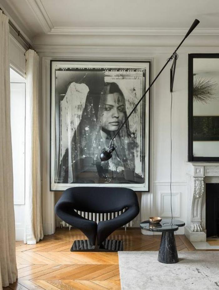 amenagement salon avec parquet en jaune, grande photographie portrait de femme Afghane, style ethno, cheminée blanche, fauteuil design en noir en tissu et base en marbre noir , tapis en noir et blanc